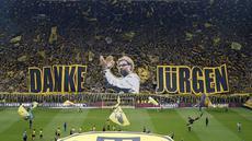 Suporter Borussia Dortmund membentangkan spanduk raksasa berwajah Juergen Klopp dan tulisan 'Danke Jurgen' (terima kasih Jurgen), sebelum laga kontra Werder Bremen di pekan terakhir Bundesliga Jerman, Sabtu (23/5) malam WIB. (AP Photo/Frank Augstein)