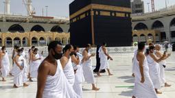 Umat muslim mengelilingi Kakbah mengenakan masker dan menjaga jarak untuk membantu menghentikan penyebaran virus corona COVID-19 saat pelaksanaan umrah di Masjidil Haram, Makkah, Arab Saudi, Minggu (30/5/2021). (AP Photo/Amr Nabil)