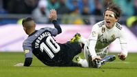 Gelandang Real Madrid, Luka Modric, terjatuh saat berebut bola dengan pemain Sevilla, Ever Banega, pada laga La Liga di Stadion Santiago Bernabeu, Sabtu (19/1). Real Madrid menang 2-0 atas Sevilla. (AP/Andrea Comas)