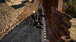 Nelly, imigran Meksiko dari Oaxaca, melompati pagar perbatasan untuk masuk ke sisi AS ke San Diego, California, (28/12). Aksi imigran ilegal ini dilakukan demi bisa menembus perbatasan AS yang semakin ketat. (AP Photo/Daniel Ochoa de Olza)