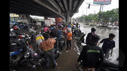 Sejumlah Pengendara Motor saat berada dibawah jembatan untuk memperbaiki motor yang mati akibat banjir, Jakarta, Senin (6/2/2015).  Hujan yang turun sejak malam hingga kini membuat sejumlah ruas jalan tergenang air. (Liputan6.com/Faizal Fanani)