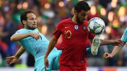 Gelandang Portugal, Bernardo Silva, berusaha melewati bek Belanda, Daley Blind, pada laga final UEFA Nations League di Stadion Dragao, Porto, Minggu (9/6). Portugal menang 1-0 atas Belanda. (AFP/Gabriel Bouys)