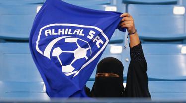Seorang wanita mengibarkan bendera saat mendukung tim Al-Hilal dari Saudi melawan Al-Ittihad dalam pertandingan Liga Saudi Pro di King Fahd International Stadium di Riyadh (13/1). (AFP Photo/Ali Al-Arifi)