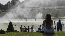 Sejumlah warga bermain di kolam air mancur di Trocadero Fountains dekat Menara Eiffel, Paris (22/7/2019). Warga Paris bersiap menghadapi suhu terpanas pada minggu ini ketika gelombang panas akan melanda ke Eropa utara. (AFP Photo/Alain Jocard)
