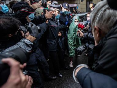 Petugas bantuan Italia bernama Silvia Romano yang dibebaskan oleh militan Somalia, dikawal polisi Italia (Carabinieri), tiba di rumahnya di Milan, 11 Mei 2020. Silvia, 25 tahun, memutuskan masuk Islam setelah dirinya diculik dari kota pesisir tenggara Kenya pada November 2018. (AP/Luca Bruno)