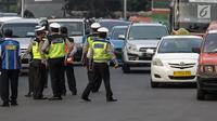 Petugas polisi mengatur lalu lintas saat pemberlakuan sistem ganjil genap di pintu masuk Gardu Tol Cibubur 2, Jakarta, Senin (16/4). Aturan ganjil genap ini diujicobakan di Gerbang Tol pada  Senin 16 April 2018. (Liputan6.com/Faizal Fanani)