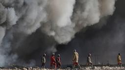 Para pekerja melihat kepulan asap kilang minyak yang dibakar oleh ISIS di Qayyara, selatan Mosul, Irak, (23/11). Sebelumnya, sekitar enam sumur minyak telah dibakar ISIS di kawasan tersebut. (REUTERS/Goran Tomasevic)