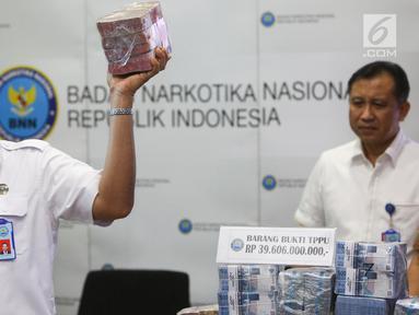 Kepala BNN Komjen Budi Waseso menunjukkan barang bukti hasil tindak pidana pencucian uang (TPPU) kasus narkoba di BNN, Jakarta, Selasa (13/6). BNN mengungkap kasus TPPU dengan total aset Rp 39 miliar dari kedua kasus berbeda. (Liputan6.com/Yoppy Renato)