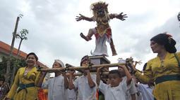 Anak-anak mengarak Ogoh-Ogoh selama atraksi Karnaval Seni Budaya Lintas Agama di kawasan Jalan Pemuda  Semarang, Minggu (25/3). Lima ogoh-ogoh yang didatangkan dari Bali ikut memeriahkan acara ini. (Liputan6.com/Gholib)
