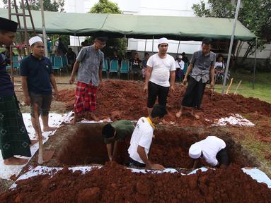 Para santri menggali lubang kubur untuk pemakaman tokoh PBNU KH Hasyim Muzadi di Kompleks Ponpes Al Hikam, Depok, Kamis (16/3). KH Hasyim meninggal dunia lantaran sakit yang dideritanya di Malang pada usia 72 tahun. (Liputan6.com/Immanuel Antonius)