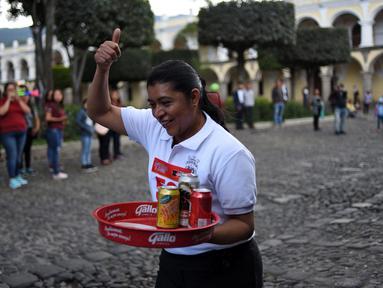 Seorang pramusaji mengacungkan jempol saat mengikuti Waiters Race ke-16 di Antigua, barat daya Ibu Kota Guatemala City, Rabu (14/11). Peserta diminta unjuk kebolehan menggunakan satu tangan membawa nampan berisi minuman. (JOHAN ORDONEZ/AFP)