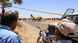 Warga melihat kondisi pesawat jet tempur Libya L-39 Albatros pasukan Khalifa Haftar di Kota Medenine di perbatasan Tunisia-Libya (22/7/2019). Pendaratan darurat jet tersebut sampai mengundang banyak perhatian warga di Kota Medenine. (AFP Photo/Fathi Nasri)