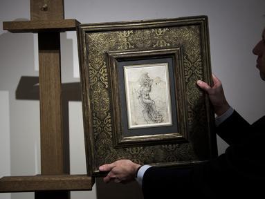 Seorang anggota Rumah Lelang Tajan menyiapkan gambar sketsa karya Leonardo da Vinci sebelum dilelang di Paris, Prancis (13/12). Leonardo da Vinci adalah seorang seniman yang dikenal dengan lukisan 'Mona Lisa'. (AFP/Philippe Lopez)