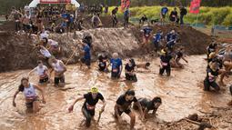 Sejumlah peserta tercebur di kolam lumpur saat memulai perlombaan Mud Day di Tel Aviv, Israel (16/3). Sekitar 5.000 orang ikut berpartisipasi dalam lomba Hari Lumpur di Tel Aviv ini. (AFP Photo/Jack Guez)