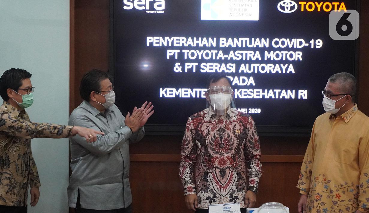 Menteri Kesehatan TerawanAgus Putranto(kedua kanan) disaksikan Presdir PT Toyota Astra Motor (TAM) Susumu Matsuda (kedua kiri) saat mencoba face shield yang merupakan bantuan dari TAM dan PT Serasi Autoraya (SERA) untuk penanganan Covid-19 di Jakarta Rabu (20/5/2020). (Liputan6.com/HO/Ady)