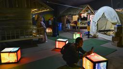 Pengunjung melihat pameran yang menggambarkan tempat perlindungan sementara di Museum Tsunami Aceh di Banda Aceh (19/10/2019). Museum ini berfungsi sebagai pengingat gempa bumi dan tsunami Samudra Hindia 2004. (AFP Photo/Chaideer Mahyuddin)