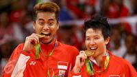 Pasangan ganda campuran Indonesia, Tontowi Ahmad dan Liliyana Natsir mengigit medali emas usai mengalahkan lawannya asal Malaysia Peng Soon Chan dan Liu Ying Goh pada final bulutangkis di Riocentro Pavilion 4 , Brasil. (REUTERS/Mike Blake)