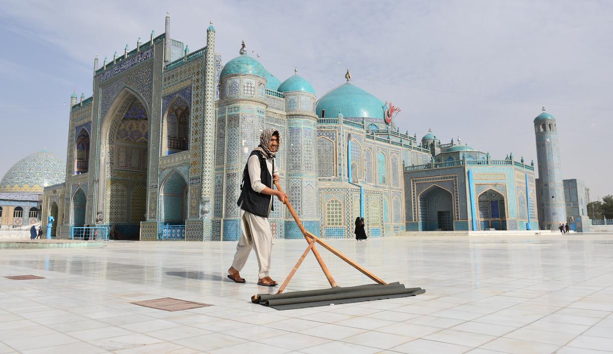 Seorang pria membersihkan halaman depan Masjid Biru di Mazar-i-Sharif, ibu kota Provinsi Balkh, Afghanistan utara (11/7/2020). Setelah lima bulan ditutup akibat dampak pandemi COVID-19, Masjid Biru baru-baru ini telah dibuka kembali untuk umum. (Xinhua/Kawa Basharat)