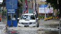 Sebuah mobil menerobos genangan air di depan kampus UKRIDA, Jakarta, Selasa (21/1). Hujan deras sejak malam tadi, membuat sejumlah wilayah Jakarta tergenang air banjir. (Liputan6.com/Gempur M Surya)