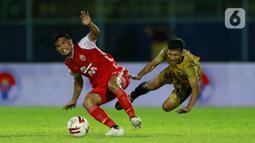 Pemain Persija Jakarta Sandi Sute (kiri) berebut bola dengan pemain Bhayangkara Solo FC TM Ichsan pada laga Piala Menpora 2021 di Stadion Kanjuruhan, Malang, Rabu (31/3/2021). Persija menang 2-1. (Bola.com/M Iqbal Ichsan)