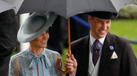 Duchess of Cambridge Kate Middleton bersama suaminya Duke of Cambridge Pangeran William mengenakan payung saat menghadiri ajang pacuan kuda Royal Ascot di Ascot, Inggris, Selasa (18/6/2019). (ADRIAN DENNIS/AFP)