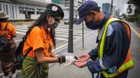 Relawan yang tergabung dalam Gerakan Jaga Indonesia aksi memyemprotkan hand sanitizer kepada pengguna jalan di Pelican Cross kawasan Thamrin, Jakarta, Senin (23/3/2020). Aksi tersebut mengajak masyarakat menjaga kebersihan tangan untuk mengurangi penyebaran Covid-19. (Liputan6.com/Faizal Fanani)