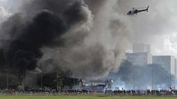 Helikopter terbang saat bentrokan antara pengunjuk rasa anti-pemerintah dengan aparat kepolisian di Brasilia, Brasil, (24/5). Massa yang menuntut pengunduran diri Presiden Michel Temer mengamuk membakar gedung kementerian pertanian (AP Photo/Eraldo Peres)