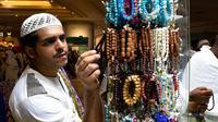 Jemaah haji memilih gelang yang dipajang di sebuah toko di kota suci Makkah, Arab Saudi pada Selasa (6/8/2019). Puncak Ibadah haji masih beberapa hari lagi, namun jemaah sudah memborong aneka barang antara lain tasbih, baju, teko emas, kurma, sajadah, minyak wangi, dan lainnya. (FETHI BELAID/AFP)