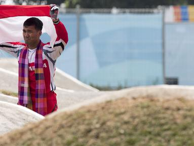 Pebalap sepeda BMX Indonesia, I Gusti Bagus Saputra, mengibarkan bendera usai berlaga pada Asian Games di Pulomas BMX Center, Jakarta, Sabtu (25/8/2018). Bagus Saputra meraih medali perak dengan catatan waktu 34,314 detik. (Bola.com/Peksi Cahyo)