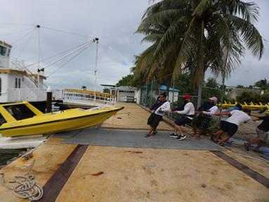 Sejumlah orang memindahkan sebuah perahu saat Badai Delta mendekati Puerto Morelos, Negara Bagian Quintana Roo, Meksiko, 6 Oktober 2020. Status Badai Delta naik menjadi topan tropis kategori 4 pada Selasa (6/10) pagi waktu setempat ketika bergerak menuju Mexican Caribbean. (Xinhua/Mauricio Collado)
