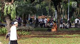 Salah satu peserta aksi membaca Al-Quran di taman pembatas Jalan Medan Merdeka Barat, Jakarta, Jumat (14/6/2019). Massa berkumpul menyampaikan pendapat terkait sidang perselisihan hasil pilpres 2019. (Liputan6.com/Helmi Fithriansyah)