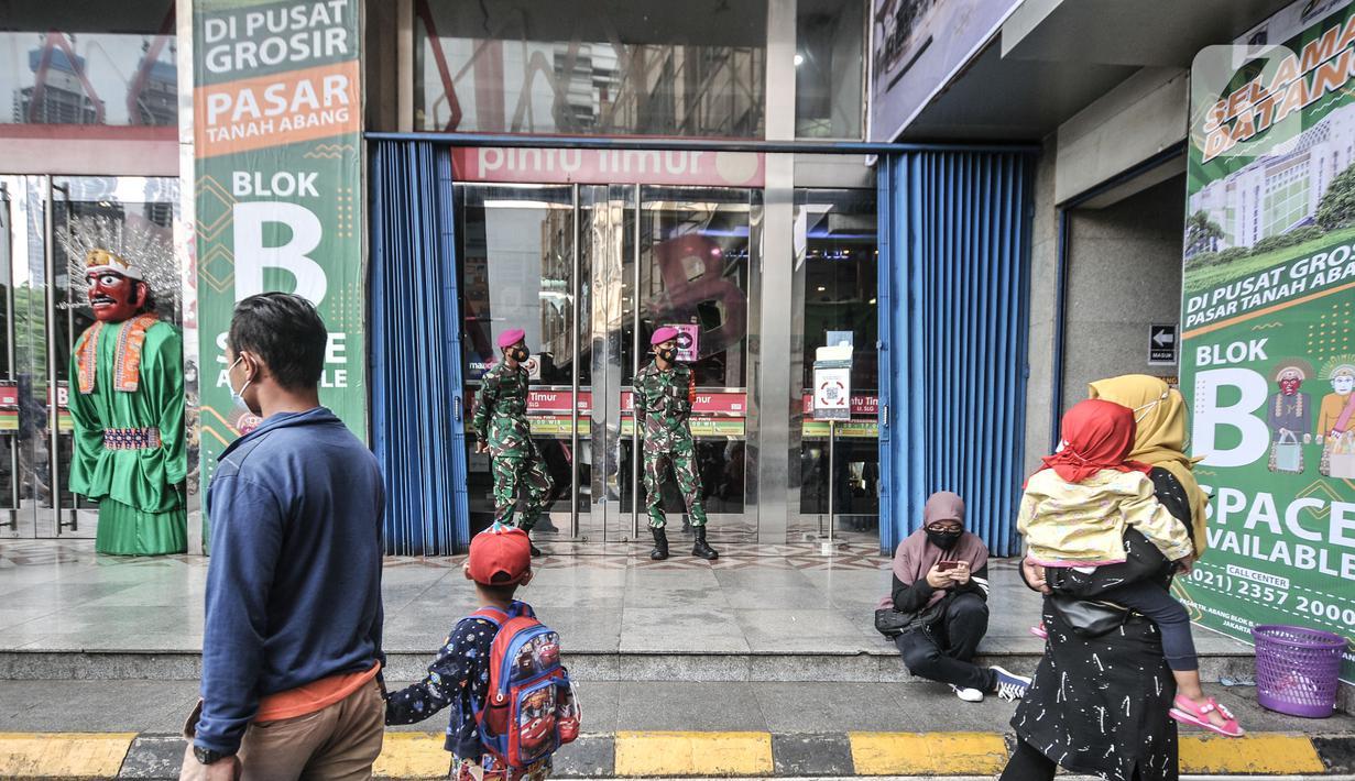 Anggota TNI berjaga di salah satu pintu masuk Blok B Pasar Tanah Abang, Jakarta, Minggu (2/5/2021). Petugas gabungan TNI, Polri, dan Satpol PP memperketat penjagaan di tiap pintu masuk Blok A dan B Pusat Grosir Tanah Abang guna mencegah kerumunan pengunjung. (merdeka.com/Iqbal S Nugroho)