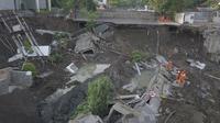 Petugas pemadam kebakaran memeriksa kondisi tanah amblas di Jalan Raya Gubeng, Surabaya, Rabu (19/12). Jalan raya tersebut amblas sedalam sekitar 20 meter dengan lebar 30 meter pada Selasa malam. (Liputan6.com/Pool/FB Dishub Kota Surabaya)