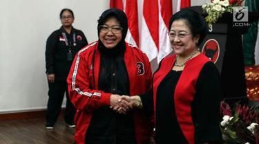 Ketua Umum PDIP Megawati Soekarnoputri (kedua kiri) menjabat tangan Ketua Bidang Kebudayaan DPP PDIP Tri Rismaharini yang dilantik di Kantor DPP PDIP, Jakarta, Senin (19/8/2019). Risma resmi menjabat sebagai Ketua Bidang Kebudayaan DPP PDI Perjuangan masa bakti 2019-2024. (Liputan6.com/Johan Tallo)