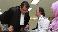 Mandra Naih (kanan) saat berbincang dengan kuasa hukumnya sebelum  menjalani sidang lanjutan di Pengadilan Tipikor, Jakarta, Senin (31/8/2015). Sidang ini beragendakan pembacaan eksepsi atau nota keberatan dari terdakwa. (Liputan6.com/Herman Zakharia)