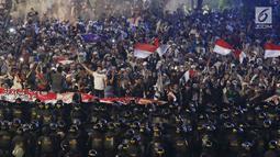 Massa aksi Gerakan Nasional Kedaulatan Rakyat dihadang oleh aparat keamanan saat melakukan aksi usai berbuka puasa dan salat maghrib berjemaah di perempatan sekitar Gedung Bawaslu, Jakarta, Rabu (22/5/2019). (Liputan6.com/Helmi Fithriansyah)