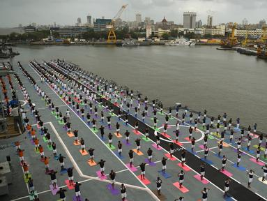 Sejumlah Personel Angkatan Laut India saat mengikuti yoga bersama menandai Hari Yoga Internasional di atas kapal induk INS Viraat di pelabuhan Mumbai, India, (21/6). Olahraga yoga telah menyatukan dunia dengan India. (AFP Photo/Punit Paranjpe)