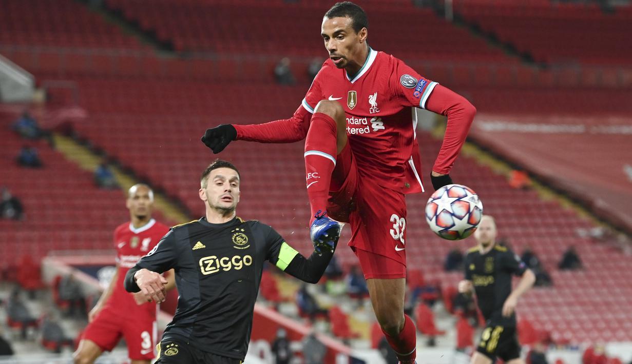 Bek Liverpool, Joel Matip melakukan penyelamatan sebelum penyerang Ajax, Dusan Tadic mencoba mencetak gol pada matchday kelima Grup D Liga Champions di Anfield, Selasa (1/12/2020). Curtis Jones mencetak gol satu-satunya yang membawa Liverpool melaju ke babak 16 besar. (Paul Ellis/Pool via AP)