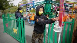 Seorang pengunjung membersihkan tangannya usai menaiki wahana di Playland Amusement Park, di Vancouver, British Columbia, Kanada, pada 10 Juli 2020. Playland Amusement Park dibuka kembali untuk umum pada Jumat (10/7), dengan langkah-langkah protokol kesehatan. (Xihua/Liang Sen)
