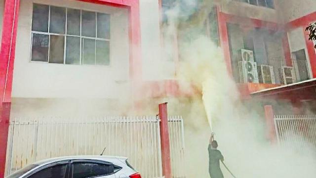 Petugas berusaha memadamkan api di gedung Telkomsel Pekanbaru yang terbakar.
