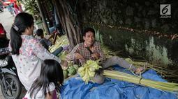 Pedagang melayani pembeli kulit ketupat di Pasar Palmerah, Jakarta, Senin (2/6/2019). Jelang lebaran penjualan kulit ketupat mulai ramai, omsetnya melonjak hingga 10 kali lipat. (Liputan6.com/Faizal Fanai)