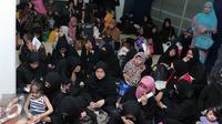 Sejumlah Tenaga Kerja Indonesia (TKI) menunggu bus di Bandara Soekarno Hatta,Tangerang, Rabu (11/11). Sebanyak 450 WNI overstayers dan TKI undocumented dari Jeddah, Arab Saudi dipulangkan pemerintah Indonesia. (Liputan6.com/Angga Yuniar)