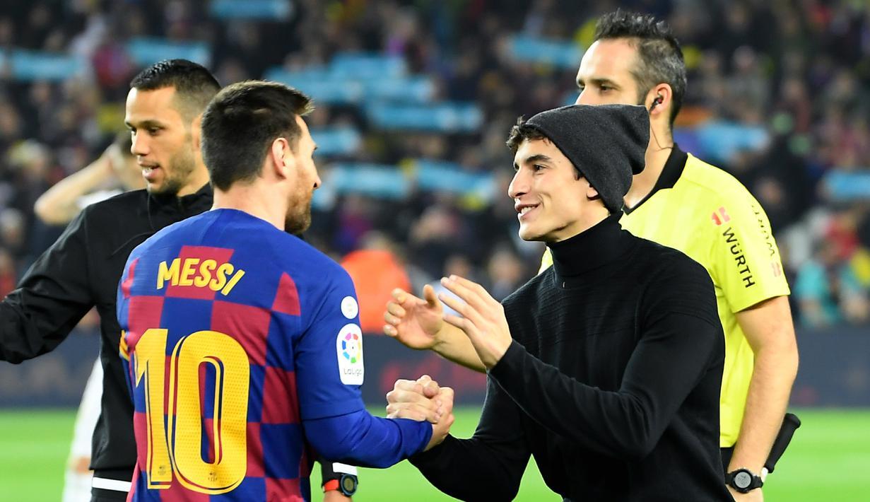 """Pembalap Repsol Honda, Marc Marquez (kanan) bersalaman dengan penyerang Barcelona, Lionel Messi sebelum pertandingan Liga Spanyol """"El Clasico"""" antara Barcelona melawan Real Madrid di Camp Nou Stadium (18/12/2019). Marc Marquez diketahui merupakan penggemar berat Barcelona. (AFP/Lluis Gene)"""