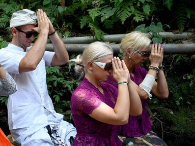 Turis Ceko, Sabina Dolezalova (dua kanan) dan Zdenek Slouka (dua kiri) mengikuti upacara guru piduka di Pura Beji, Ubud, Bali, Kamis (15/8/2019). Pasangan kekasih ini menjalani upacara penyucian pura usai berulah dengan cebok menggunakan air suci di pancuran Pura Beji. (SONNY TUMBELAKA/AFP)