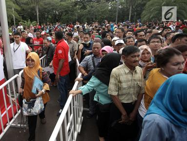 Petugas mengatur warga yang mengantre untuk membuat paspor dalam acara Festival Keimigrasian 2018 di Lapangan Barat Daya Monas, Jakarta, Minggu (21/1). Para pembuat paspor mengantre sejak pagi. (Liputan6.com/Arya Manggala)