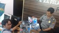 Jurnalis dari Goal Indonesia, Budi Cahyono (kiri) saat menunjukkan bukti foto intimidasi oleh pemain PSIM Yogyakarta, Achmad Hisyam Tolle di Mapolda DIY, Rabu (23/10/2019). (Bola.com/Vincentius Atmaja)