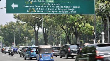 Kendaraan melintas di bawah rambu pemberitahuan sistem ganjil genap di Jalan Medan Merdeka Utara, Jakarta, Senin (3/9). Pemprov DKI Jakarta melalui Pergub Nomor 92 Tahun 2018 memperpanjang waktu sistem ganjil genap. (Merdeka.com/Iqbal S. Nugroho)