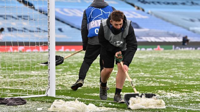 Petugas membersihkan salju yang menutupi rumput jelang laga Manchester City melawan PSG pada laga semifinal Liga Champions di Stadion Etihad, Rabu (5/5/2021). (AFP/Paul Ellis)