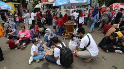 Pengunjung menikmati makan sambil lesehan jelang Closing Ceremony Asian Games 2018 di kawasan Gelora Bung Karno, Jakarta, Minggu (2/9). Mereka mengisi perut sebelum Closing Ceremony. (Liputan6.com/Fery Pradolo)
