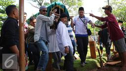 Kerabat menggotong keranda istri artis komedi dan pembawa acara Tukul Arwana, Susiana, saat dimakamkan di TPU Tanah Kusir, Jakarta, Rabu (24/8). Susiana wafat di usia 48 tahun akibat penyakit asma yang dideritanya. (Liputan6.com/Immanuel Antonius)
